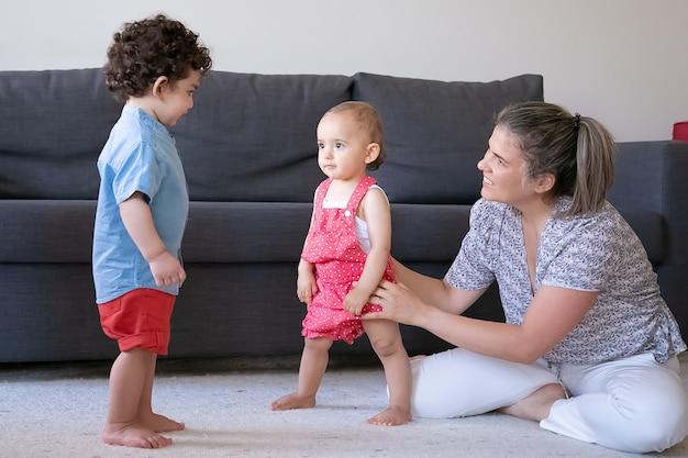 Gelukkige moeder spelen met kleine kinderen thuis en zitten met gekruiste benen. schattige babymeisje en jongen permanent blootsvoets op tapijt in de woonkamer. familie binnenshuis, weekend en jeugdconcept