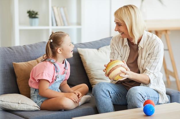 Gelukkige moeder toont het model van de planeten aan haar dochter met het syndroom van down en ze lachen zittend op de bank thuis
