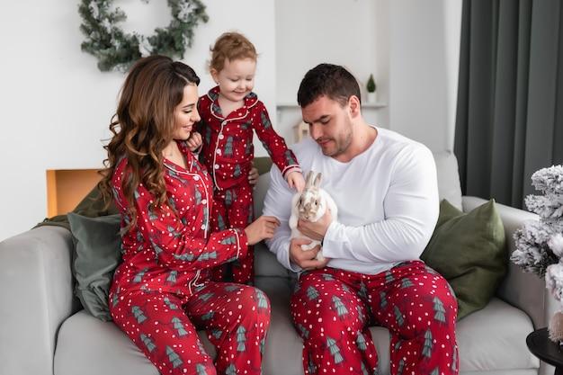 Gelukkige moeder, vader en dochter verheugen zich over het witte pluizige konijn de ochtend voor kerstmis