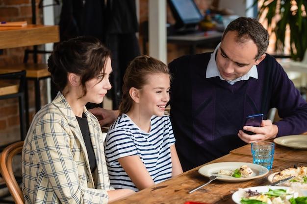 Gelukkige moeder, vader en hun meisje eten en praten in een restaurant of café