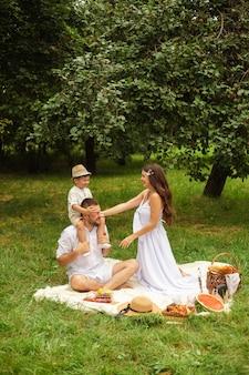 Gelukkige moeder, vader en hun schattige zoontje hebben picknick in zomerpark. kind zittend op de schouders van zijn vader. familie- en vrijetijdsconcept