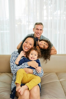 Gelukkige moeder, vader en hun twee kleine kinderen die thuis samen spelen