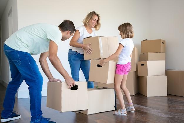 Gelukkige moeder, vader en kind houden kartonnen dozen en verhuizen naar een nieuw huis of appartement