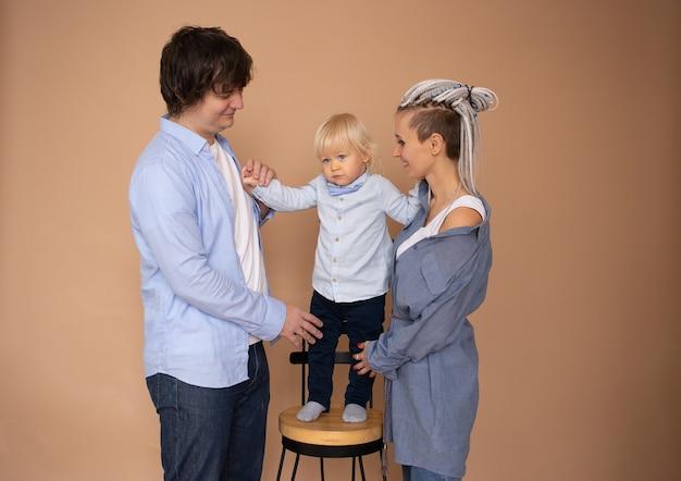 Gelukkige moeder, vader en zoontje geïsoleerd op beige muur
