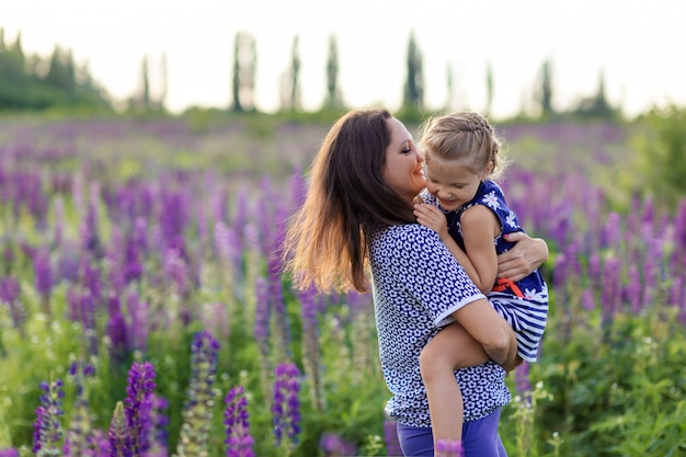 Gelukkige moeder velen omhelst haar dochter op een bloeiende lupine veld. moederdag concept
