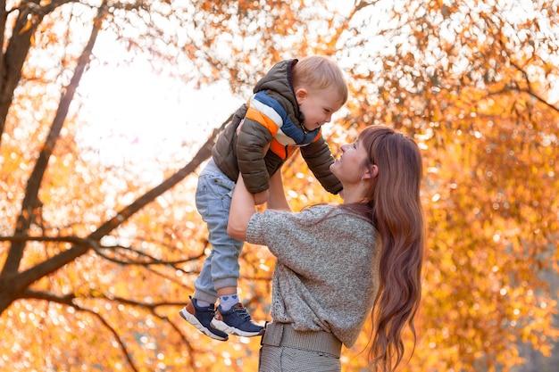 Gelukkige moeder voedt haar babyjongen met gouden loofbomen in de herfst op een zonnige dag. kopieer ruimte