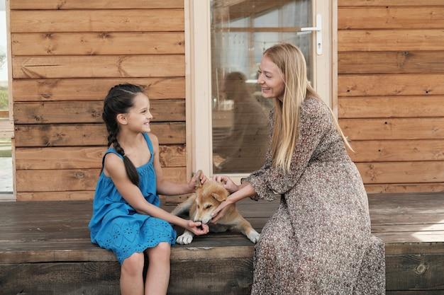 Gelukkige moeder zittend op de veranda samen met haar dochter en ze spelen met de hond