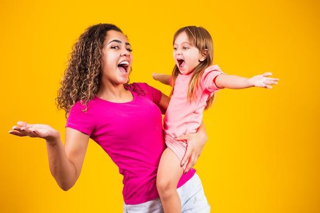 Gelukkige moederdag! aanbiddelijk kaukasisch kind met zijn moeder op gele achtergrond.