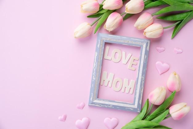 Gelukkige moederdag concept. roze tulp bloem met papieren hart en fotolijst