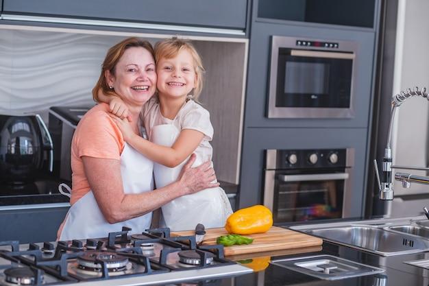 Gelukkige moederdag! kind dochter en moeder koken en plezier hebben in de keuken thuis. familie vakantie en samenzijn.