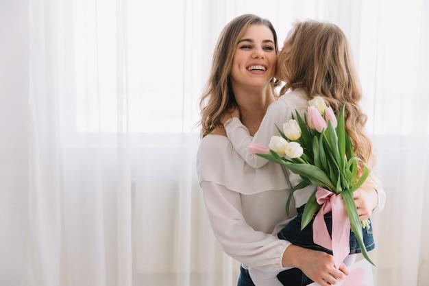 Gelukkige moederdag. kind dochter feliciteert moeders en geeft haar bloemen tulpen.