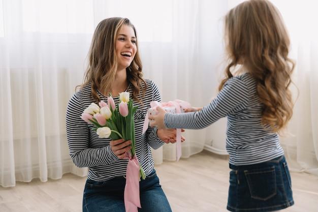 Gelukkige moederdag. kind dochter feliciteert moeders en geeft haar een geschenk en bloemen tulpen.
