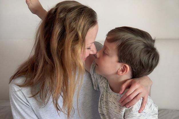 Gelukkige moederdag. kind jongen feliciteert moeder en geeft haar bloemen tulpen en ansichtkaart. moeder en zoon glimlachen en knuffelen. familie vakantie en samenzijn. moederdag groet concept.