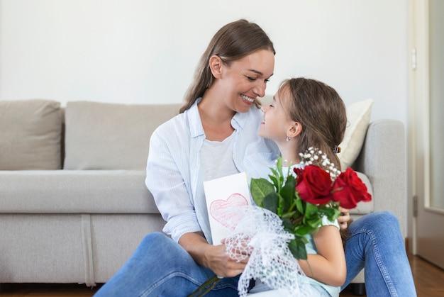 Gelukkige moederdag! kinddochter feliciteert moeder en geeft haar ansichtkaart en bloemen. moeder en meisje glimlachen en knuffelen. familie vakantie en samenzijn.