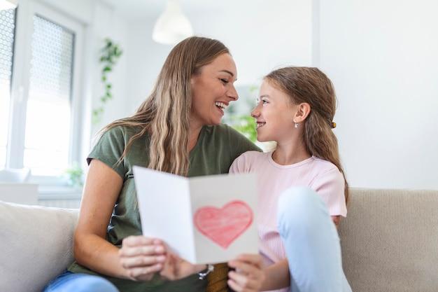 Gelukkige moederdag! kinddochter feliciteert moeder en geeft haar ansichtkaart. moeder en meisje glimlachen en knuffelen. familie vakantie en samenzijn.