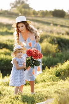 Gelukkige moederdag. kinddochter feliciteert moeder en geeft haar een boeket bloemen buitenshuis.