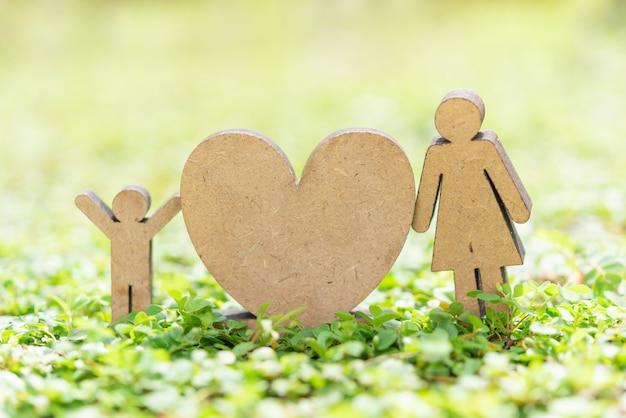 Gelukkige moederdag met hartpictogram, vrouw en jong geitjemodel staan op vers groen gras in tuin met exemplaarruimte voor tekst
