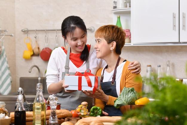 Gelukkige moederdag! tienerdochter feliciteert moeder en geeft een geschenk in de keuken thuis