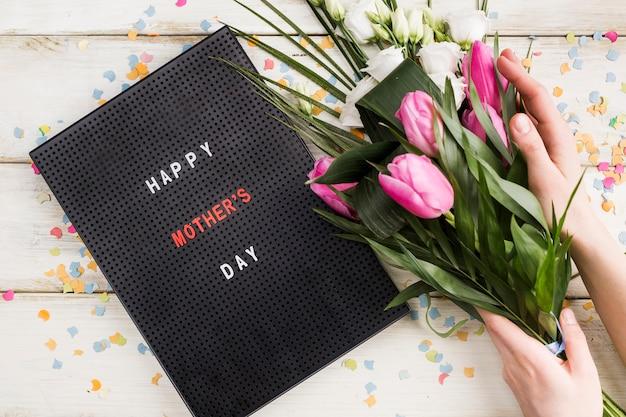 Gelukkige moederdagdagstitel aan boord met het boeket van de persoonsholding