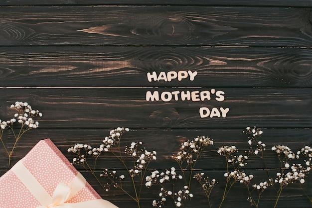 Gelukkige moederdaginschrijving met gift en bloemtakken