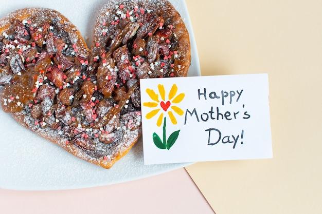 Gelukkige moederdagkaart met een bloem erop getekend over een hartvormige cake op houtachtergrond