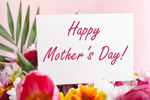 Gelukkige moederdagtekst op geschenkenkaart in bloemboeket op roze kleurenachtergrond