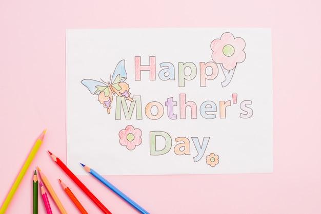 Gelukkige moedersdag die op papier met potloden trekken