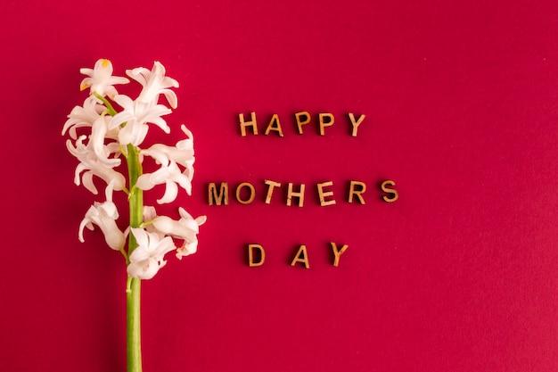 Gelukkige moedersdaginschrijving dichtbij bloem