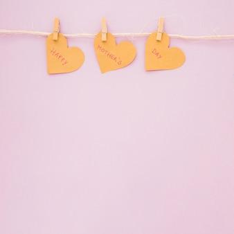 Gelukkige moedersdaginschrijving op harten die op kabel hangen