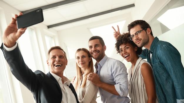 Gelukkige momenten groep lachende collega's die selfie maken en gebaren terwijl ze in de moderne staan
