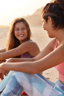Gelukkige momenten in het leven. vrolijke jonge vriendin geniet van recreatietijd, kijkt positief naar goede vriend
