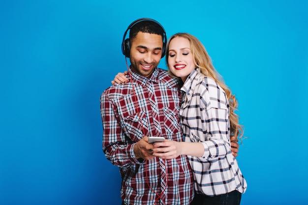 Gelukkige momenten van vreugdevolle paar luisteren naar muziek. plezier hebben, telefoon gebruiken, hobby, weekends, vrije tijd, genieten van liedjes, positiviteit uiten, glimlachen, geliefden.