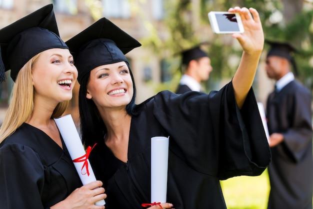 Gelukkige momenten vastleggen. twee gelukkige vrouwen in afstudeerjurken die selfie maken en glimlachen terwijl twee mannen op de achtergrond staan