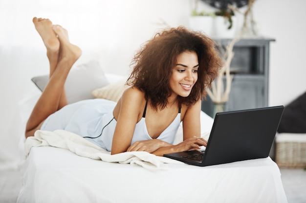 Gelukkige mooie afrikaanse vrouw in nachtkleding die op bed liggen die thuis het glimlachen laptop bekijken.