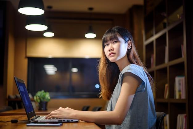 Gelukkige mooie aziatische studentenvrouw die aan laptop in moderne bibliotheekruimte werken