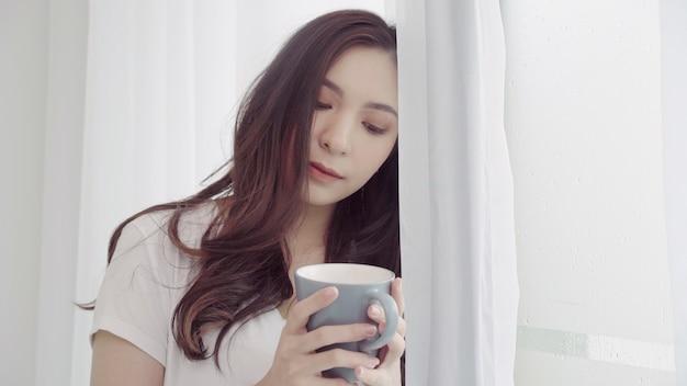 Gelukkige mooie aziatische vrouw die en een kop van koffie of thee glimlacht drinkt dichtbij het venster in de slaapkamer.