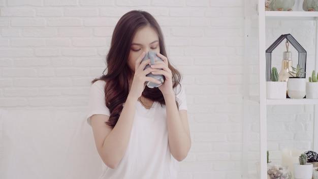 Gelukkige mooie aziatische vrouw die en een kop van koffie of thee op bed glimlacht drinkt