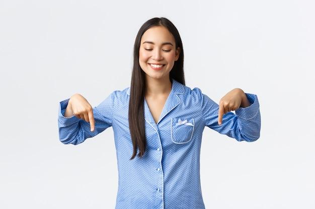 Gelukkige mooie aziatische vrouw in blauwe pyjama die en met vingers naar beneden kijkt, onderste advertentie toont, aankondiging van product maakt, staande in jam over witte muur
