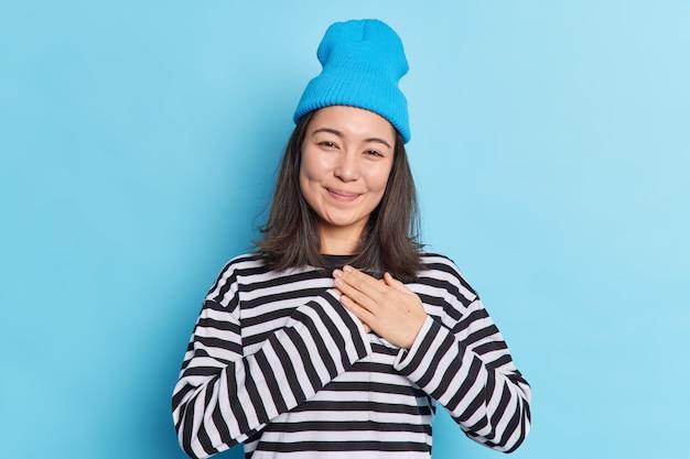 Gelukkige mooie aziatische vrouw maakt dankbaarheidsgebaar drukt handpalmen tegen het hart voelt zich aangeraakt blij met complimenten zegt bedankt uit dankbaarheid draagt blauwe hoed gestreepte trui poseert binnen