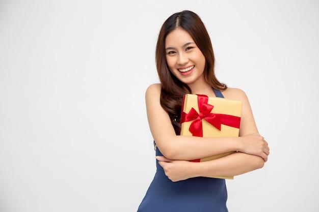 Gelukkige mooie aziatische vrouwenglimlach met gouden die giftdoos op groene muur wordt geïsoleerd. verliefde tienermeisjes, geschenken ontvangen van geliefden. nieuwjaar of kerstmis concept