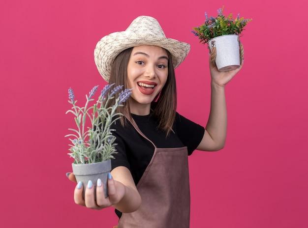 Gelukkige mooie blanke vrouwelijke tuinman met een tuinhoed met bloempottenpot
