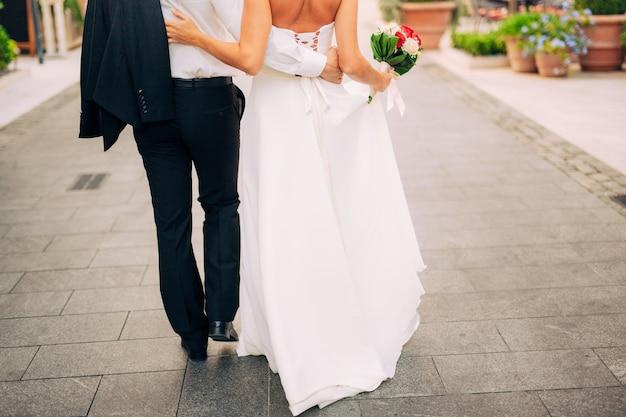 Gelukkige mooie bruid buitenshuis trouwjurk wapperen