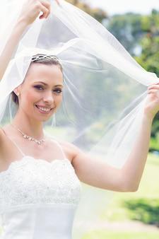 Gelukkige mooie bruid die zelf in tuin onthullen