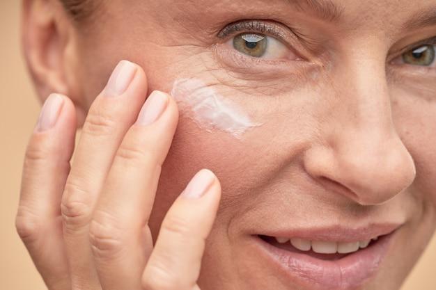Gelukkige mooie dame die anti-aging crème onder de ogen aanbrengt