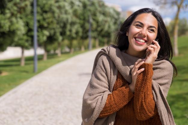 Gelukkige mooie dame die op telefoon in stadspark spreekt