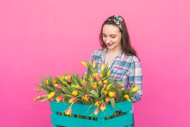 Gelukkige mooie donkerbruine kaukasische jonge vrouw met grote doos tulpen op roze muur.