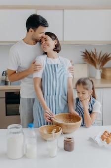 Gelukkige mooie familie in huiskeuken, vader omhelst moeder met liefde, meisje kijkt in kom, observeert hoe mama kookt en ingrediënten zwaait, eieren gebruikt om deeg te maken. huiselijke sfeer