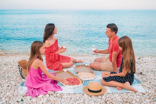 Gelukkige mooie familie op een tropisch strand met picknick samen op de zonsondergang
