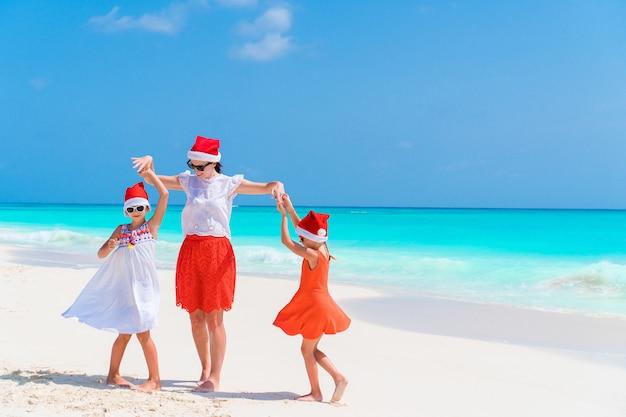 Gelukkige mooie familie van moeder en kinderen in rode kerstmuts op een tropisch strand vieren kerstmis