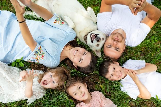 Gelukkige mooie grote familie samen moeder, vader, kinderen en hond liggend op het gras bovenaanzicht
